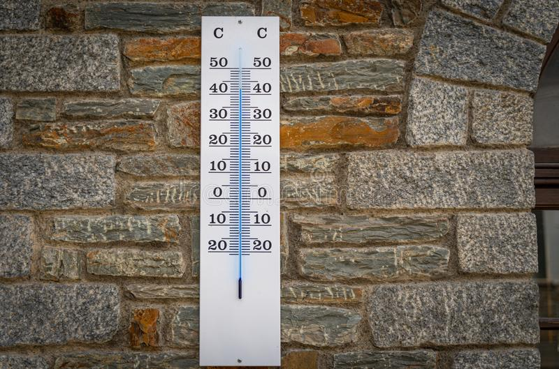Thermometer showing more than 40 degrees celsius on a stone wall, concept of world hot and weather. Thermometer showing more than 40 degrees celsius on a stone royalty free stock photos