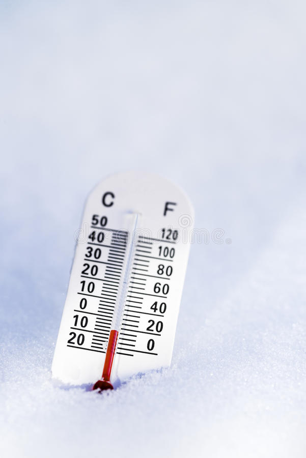 Thermometer in the snow. With focus on the red. You can see both celcius and fahrenheit stock images