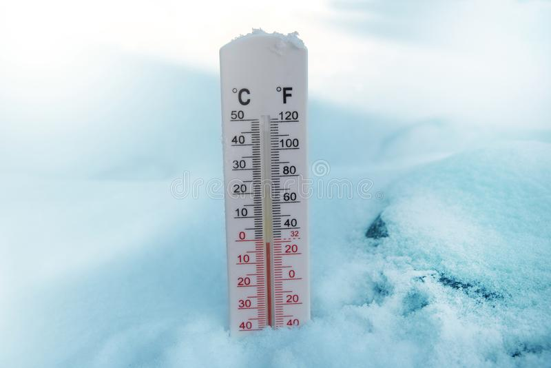 Thermometer on snow shows freezing temperature in celsius or farenheit.  royalty free stock photos