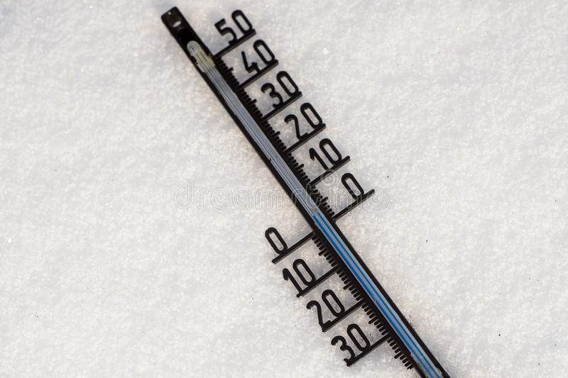 Thermometer on snow shows low temperature royalty free stock images