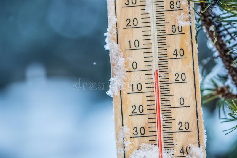 Thermometer on snow shows low temperatures in celsius or farenheit.  royalty free stock photo