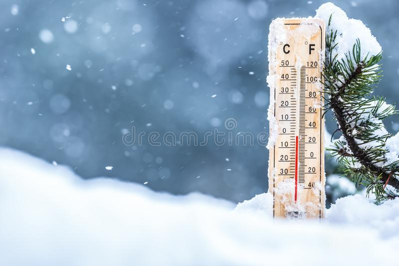 Thermometer on snow shows low temperatures in celsius or farenheit.  royalty free stock photography