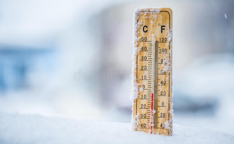 Thermometer on snow shows low temperatures in celsius or farenheit royalty free stock photo