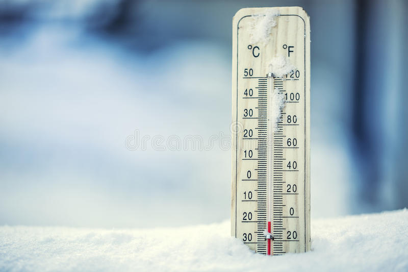 Thermometer on snow shows low temperatures under zero. Low temperatures in degrees Celsius and fahrenheit. royalty free stock image