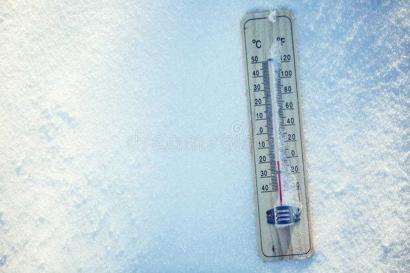 Thermometer on snow shows low temperatures under zero. Low temperatures in degrees Celsius and fahrenheit. stock image