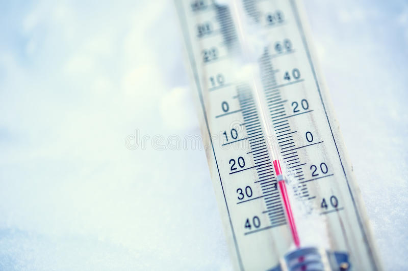 Thermometer on snow shows low temperatures under zero. Low temperatures in degrees Celsius and fahrenheit. royalty free stock photography