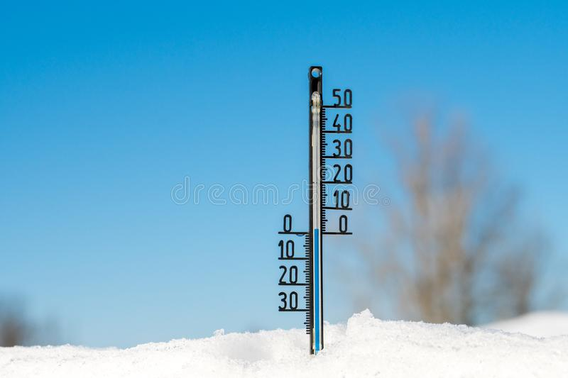 Thermometer in the snow with zero temperature under blue sky background royalty free stock photo