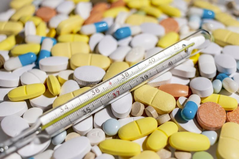 Thermometer und farbige Pillen für die Behandlung von Krankheiten und von Sucht lizenzfreie stockfotografie