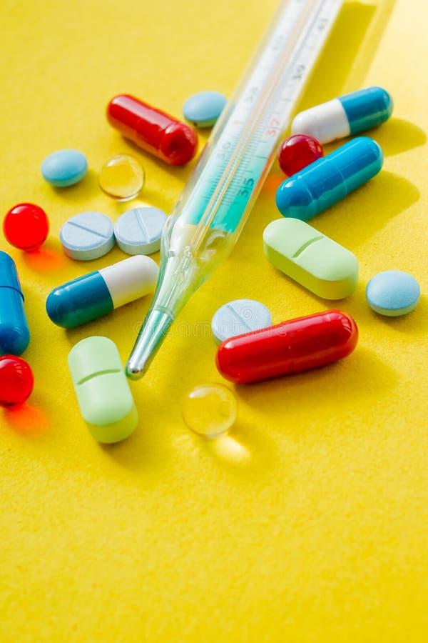Thermometer und farbige Pillen für die Behandlung von Krankheiten und von Sucht Thermometer, pharmazeutische Droge, Heilung, bunt stockfotografie