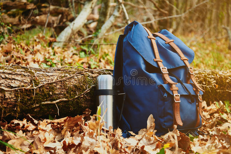 Thermos and backpack. Outdoors on autumn nature, hiking theme royalty free stock images