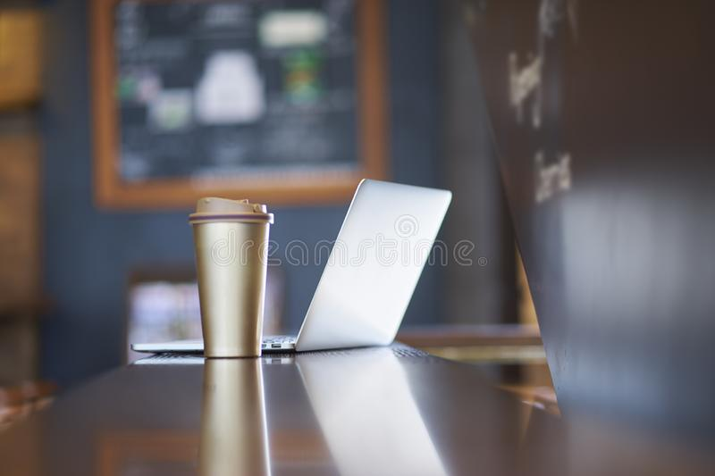 Thermos cup & laptop on table inside a coffee shop stock photo