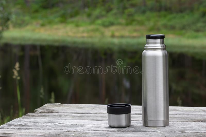 Thermos and cup on wooden table in forest near lake stock photography