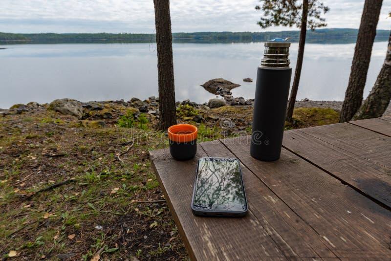 Thermos de Coffeecup et un téléphone portable à une table près d'un lac image stock