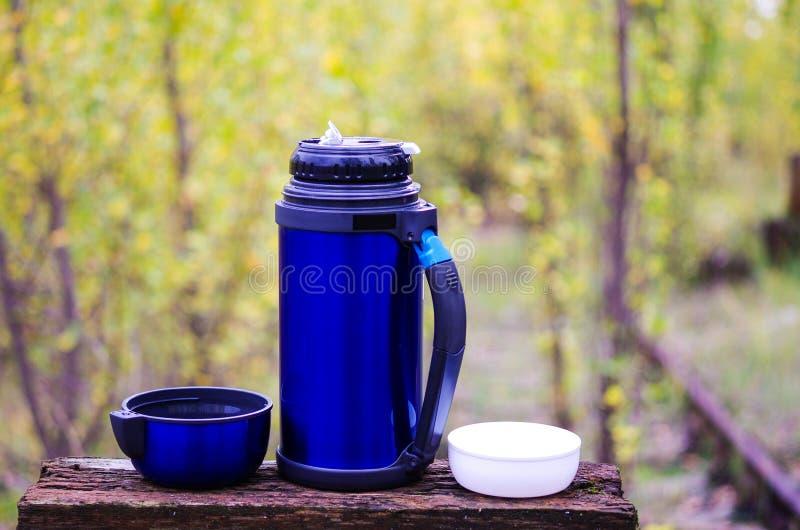 Thermos pour des boissons Thermos avec deux tasses Avec un thermos sur la nature Camper avec un thermos Automne photo libre de droits