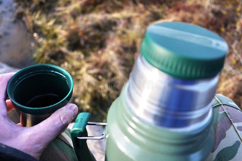 Thermos pour les boissons chaudes et froides avec la poignée Avec ce thermos vous pouvez aller trimarder images libres de droits