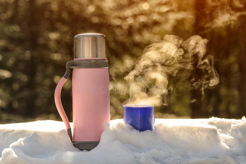 Thermos with a steaming mug of hot drink stands in the snow. Winter sunny day stock photos