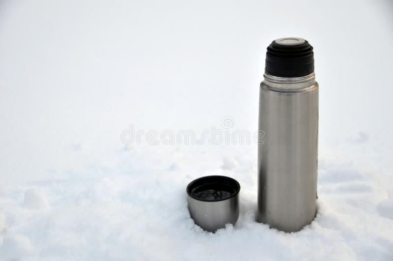 Thermos and steel tourist mug with snow white royalty free stock images