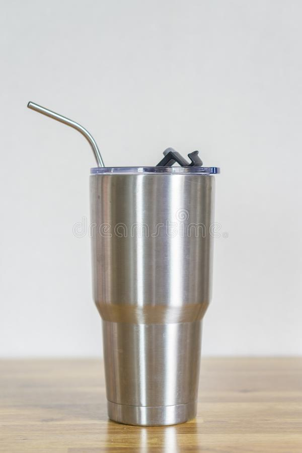 Thermos tumbler mug that made of stainless steel with metal drinking straws. On wooden table ,white background stock photo
