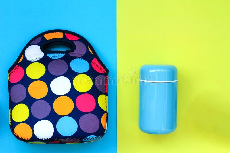 Thermosflasche weiche blaue Farbe und eine Brotdosetasche auf einem gelb-blauen Hintergrund stockbilder