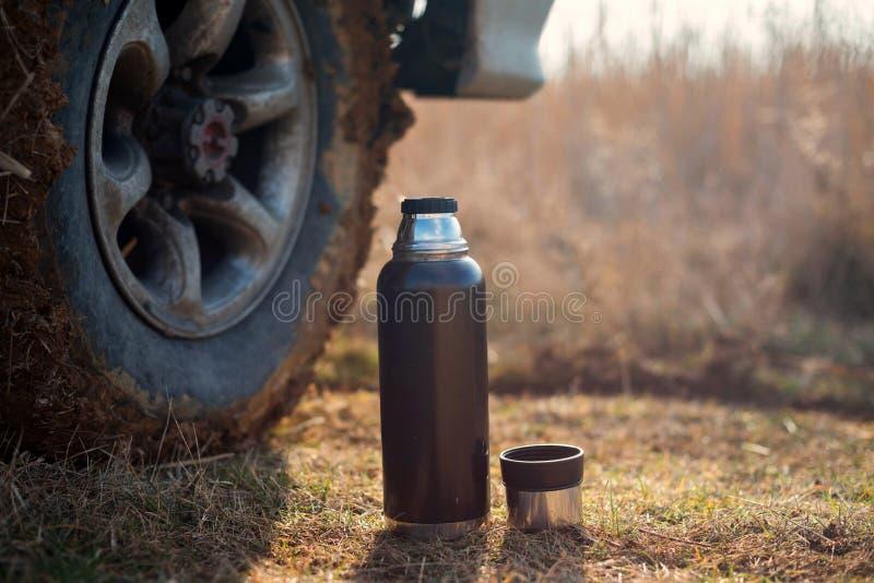 Thermosflessen op de achtergrond de wielen van SUV De rust en ontspant royalty-vrije stock foto