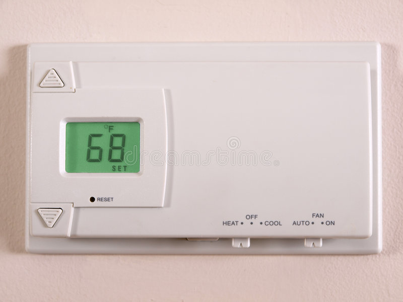 Thermostat 68 F. Wall Thermostat set at 68 degrees Farenheit stock images