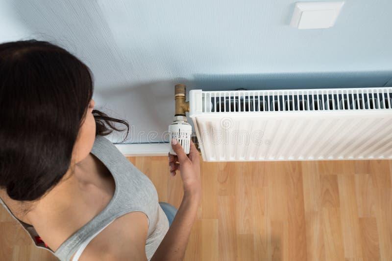 Thermostat de rotation de jeune femme sur le radiateur image libre de droits