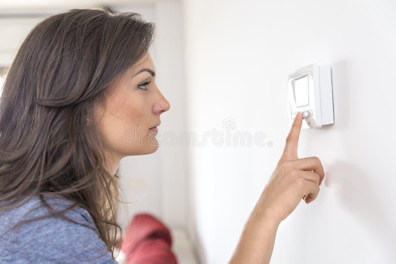 Thermostat numérique de beau bouton poussoir de femme à la maison images libres de droits
