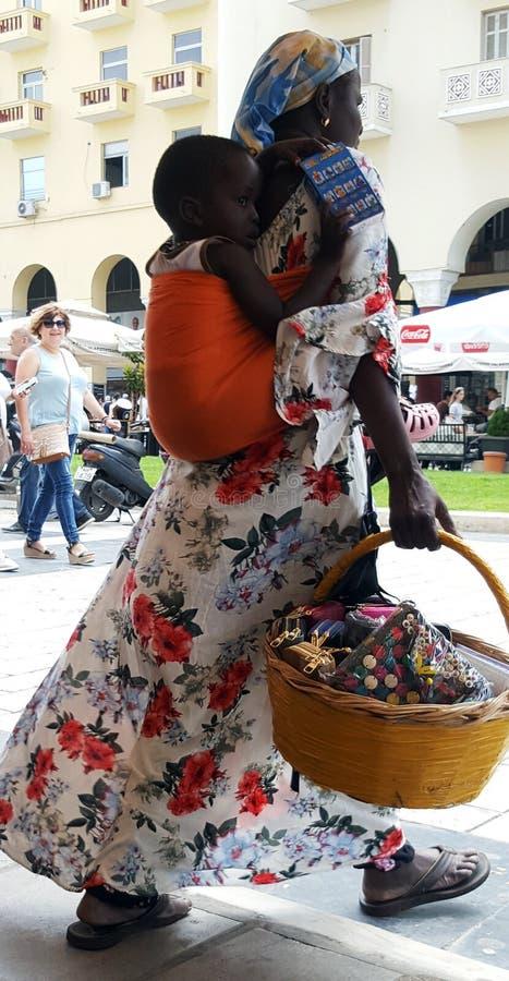THESSALONIKI, ГРЕЦИЯ - 13-ОЕ ИЮНЯ 2018: Неопознанная африканская женщина нося ее сына стоковая фотография