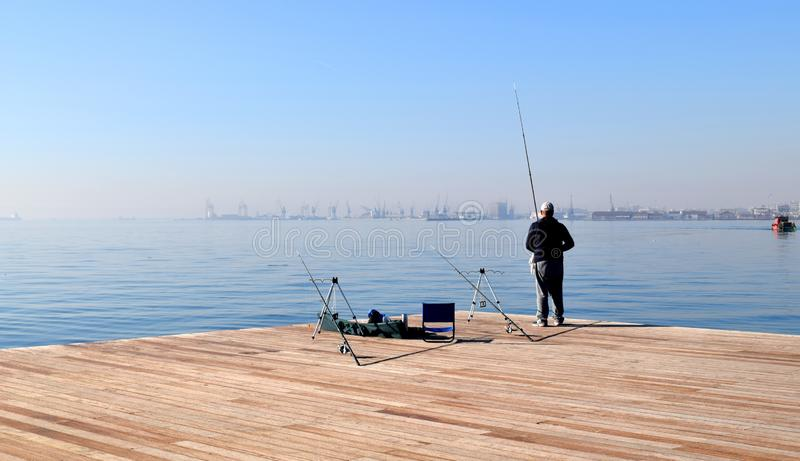 Thessaloniki, Greece - December 28 2015: Fisherman fishing in Thessaloniki seafront, Greece. stock photo