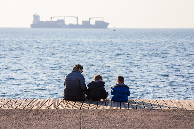 THESSALONIKI, GREECE - DECEMBER 25, 2015: Grandmother and her grandchildren resting on the Seafront, a cargo ship can be seen in t royalty free stock image