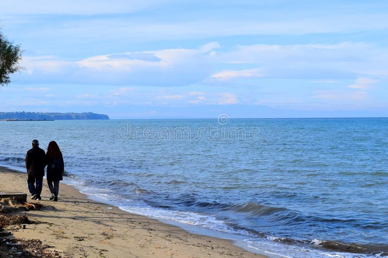 Thessaloniki, Greece - November 28 2015: Silhouettes of father and daughter walking by the sea. Blue sea landscape royalty free stock photography