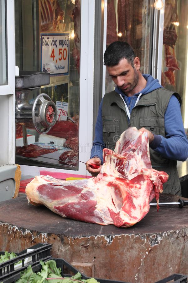 THESSALONIKI - GREECE SEPTEMBER 25,2018: Old market area, man on outdoor butchery wood slices meat royalty free stock image