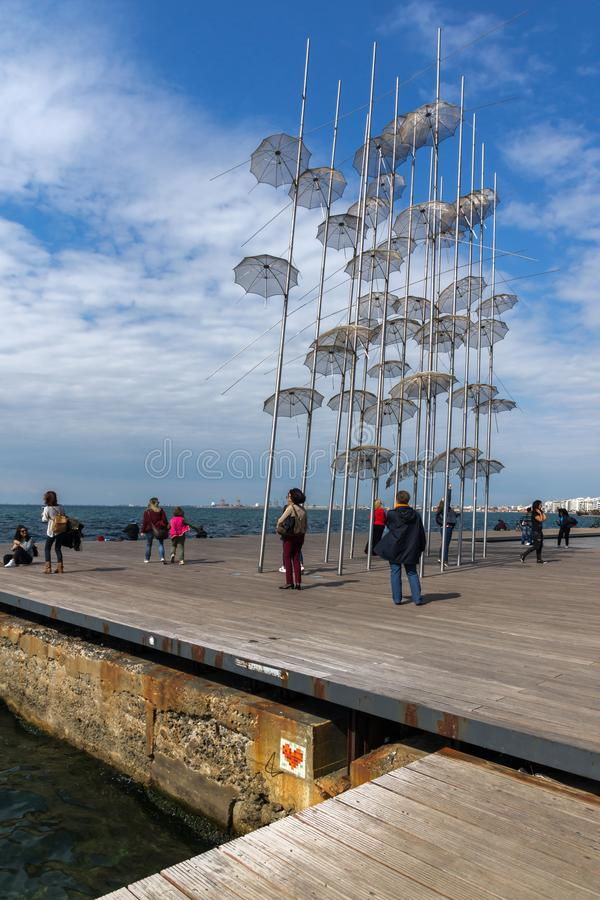 People under Umbrellas sculpture in of of city of Thessaloniki, Central Macedonia, Gre. THESSALONIKI, GREECE - SEPTEMBER 30, 2017: People under Umbrellas stock photos