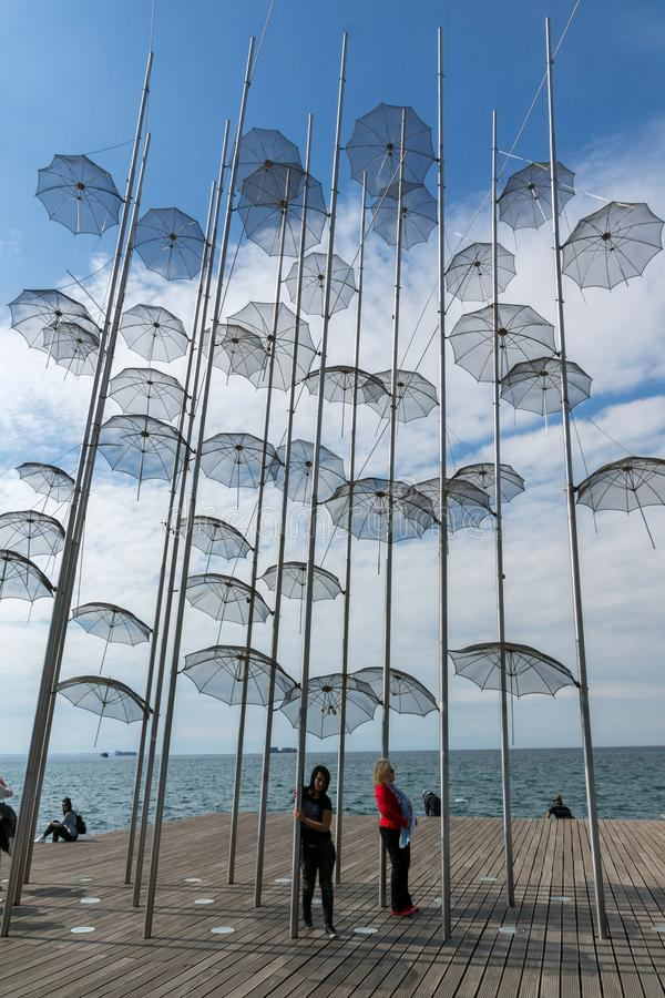 People under Umbrellas sculpture in of of city of Thessaloniki, Central Macedonia, Gre. THESSALONIKI, GREECE - SEPTEMBER 30, 2017: People under Umbrellas royalty free stock photo
