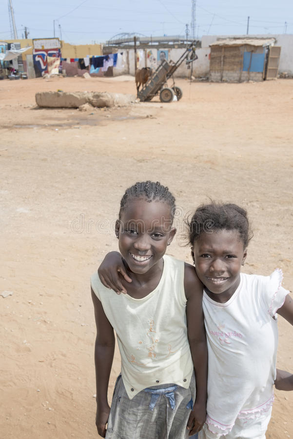 """Thiaroye, †de Senegal """"25 de julio de 2014: Dos muchachas no identificadas que se colocan en la calle, distrito popular de los  foto de archivo libre de regalías"""