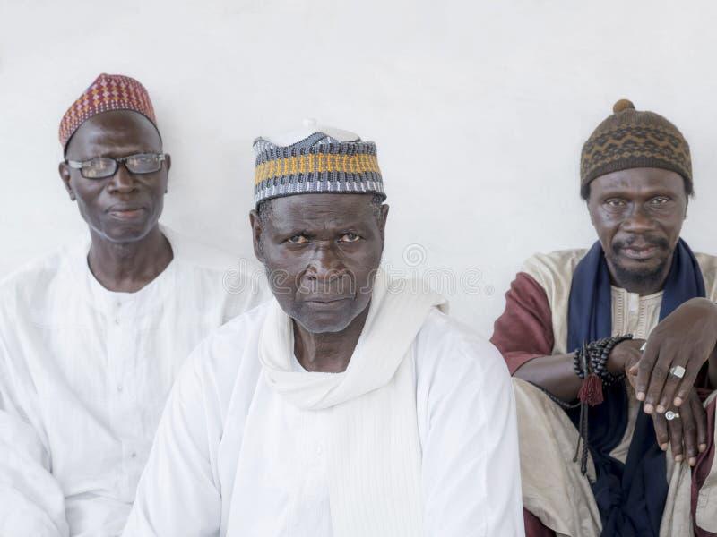 """Thiaroye, Senegal, Afrika †""""18 Juli, 2014: Niet geïdentificeerde Moslimmensen die voor de Grote Moskee van Thiaroye zitten stock afbeelding"""