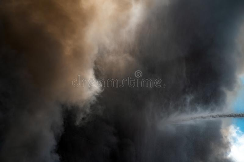 Thick black acrid smoke on the sky background. Thick black acrid smoke on the blue sky background royalty free stock photography