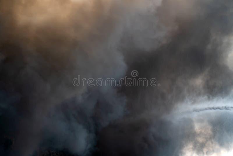 Thick black acrid smoke on the sky background. Thick black acrid smoke on the blue sky background stock image