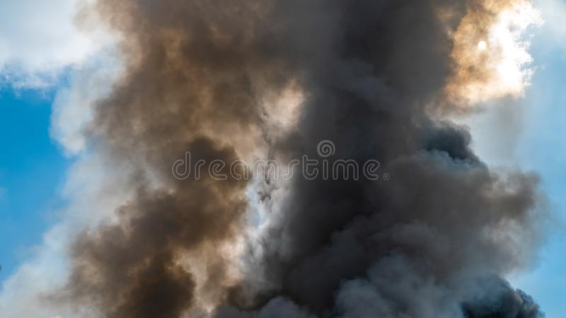 Thick black acrid smoke on the sky background. Thick black acrid smoke on the blue sky background royalty free stock image