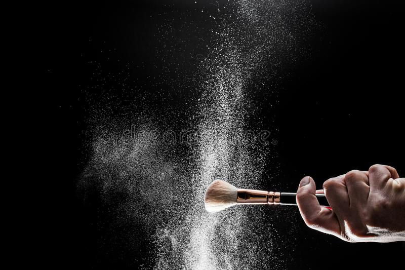 Thick black brush in motion and loose powder particles scattered around stock photos