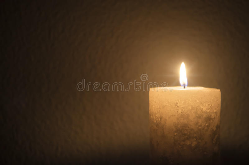A thick candle burns brightly in dark room stock photos