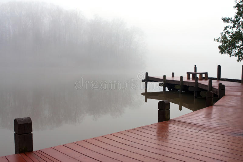 Thick Fog Covers Wooden Dock And Lake On Winter Day royalty free stock photo