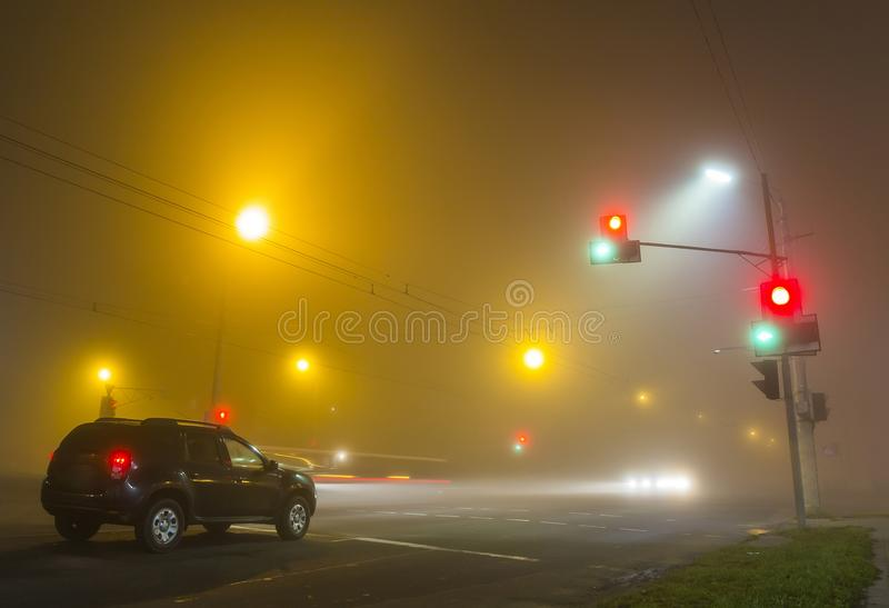 Thick fog over empty road with lonely car and traffic lights at stock photography