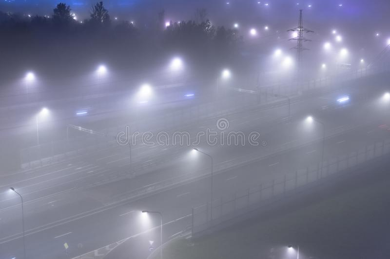 Thick fog over night highway in the city. View from above. stock photography