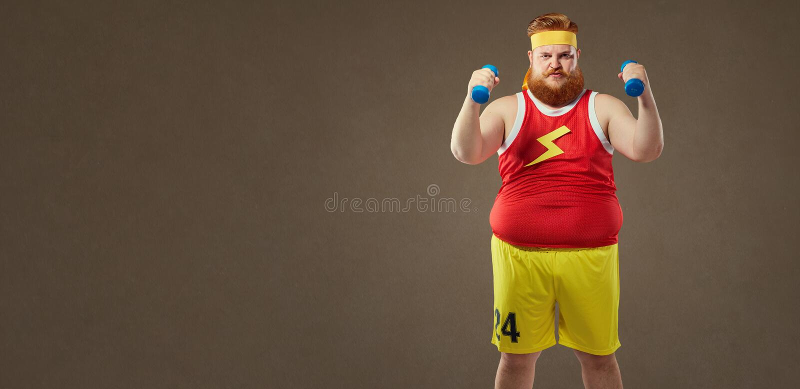 Thick funny guy in sportswear with small dumbbells.  stock photo