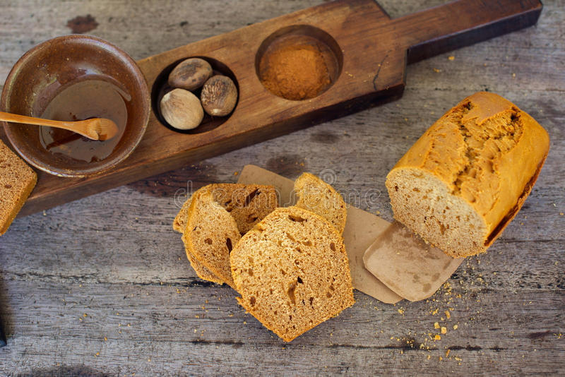 Thick gingerbread. French thick gingerbread also called pain d'epices, on rustic board with honey, nutmegs and spices stock image