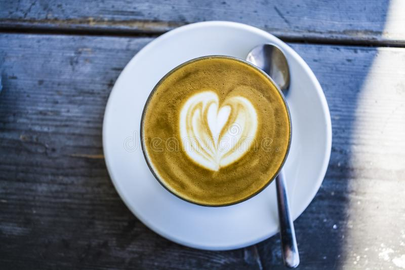 Thick glass tumbler with cappuccino and latte-art in the form heart. Ffresh coffee with milk. On a wooden table with saucer, spoon stock photo