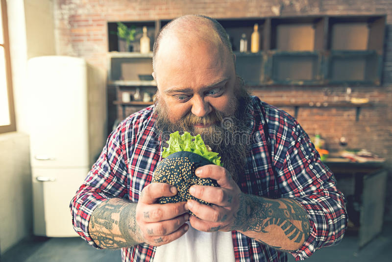 Thick guy staring at appetite sandwich royalty free stock images