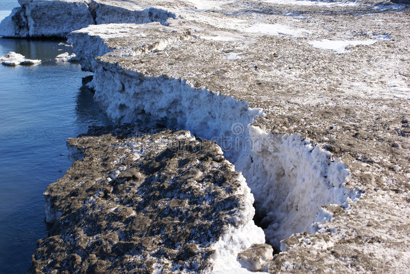 Thick ice shelf breaking off and sinking into blue water. Climate change concept stock photos