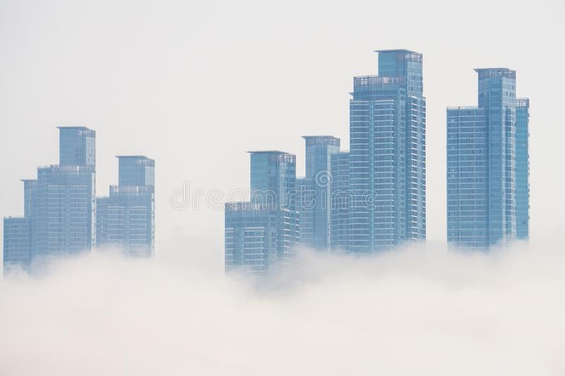 Thick large and heavy mist blow from the sea to the land and pass through skyscrapers and cover all other buildings in the area. stock image